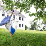 facilities - girl doing a cartwheel in the community center lawn