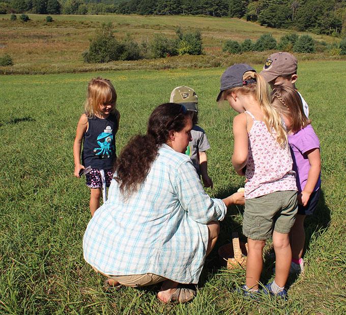 preschoolers looking at flowers in the field