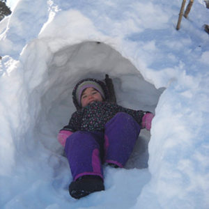 child grinning in a snow fort