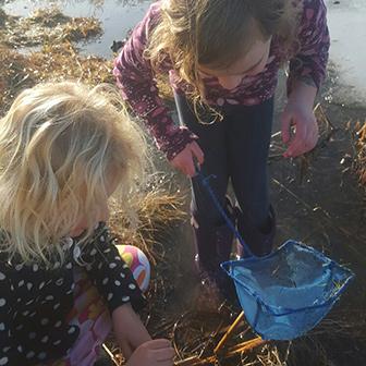 two girls marsh mucking