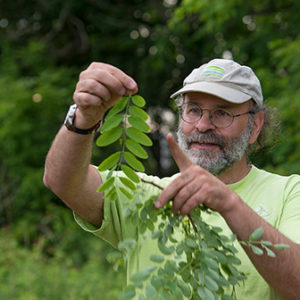 Russ Cohen pointing out a features of a plant