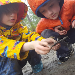 two boys squatting in mud looking at something
