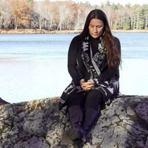 Sherri Mitchell sitting on a rock by the river