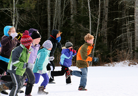 group of kids running in the snow