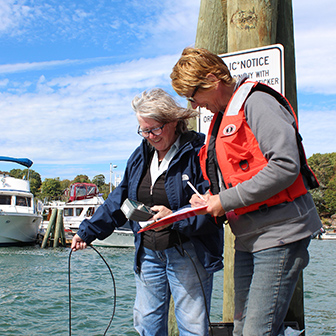 two volunteers collecting water quality data