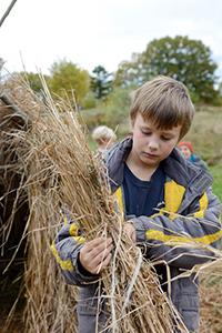 boy holding thatch bundle