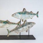 painted wooden sculpture of three mackerel