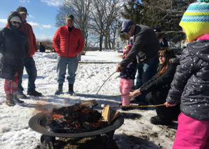 kids and parents roasting marshmallows