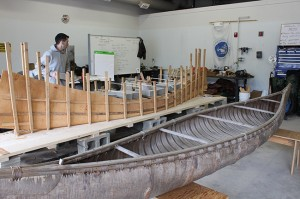 partially built canoe next to a completed craft